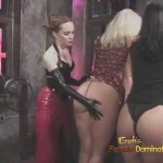 Fetish dominatrix in black PVC gloves and long red skirt, brutally spanking handsome girls