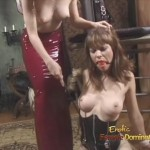 Skinny dominatrix in red latex dress punishing brunette female slave