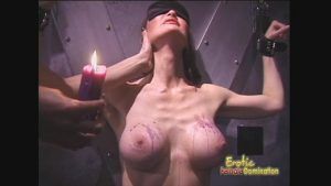 Busty Pamela is shackled before having her tits covered in hot wax