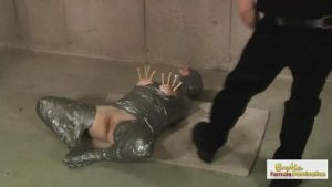 Redhead encased in plastic wrap and duct tape from head to toe