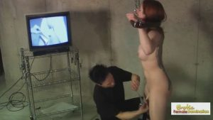 Redhead slave is bound standing and made to watch herself cum
