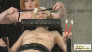 Mean Mistress covers her blonde slave in hot candle wax